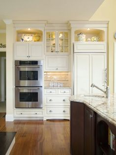 Custom cabinets w granite countertops and dark island accent, hardwood floors and stainless steel appliances #home #remodel #kitchen #bathroom #interiors  www.jimhicks.com