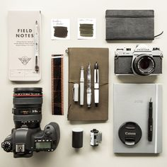 A photojournalist inspired flat lay of camera gear, fountain pens, notebooks, and ink.