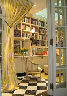 Instead of hanging a solid door separating this lovely library from the home's entrance, the designers hung a single fabric panel from the ceiling. The effect is more subtle than a door and very welcoming