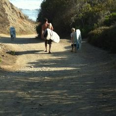 My husband heading out to surf with our boys at San Onofre.