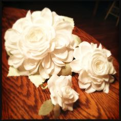Paper flower wedding bouquets and boutonnières - duchess (also known as composite) and reflexed roses in white with soft green leaves.   http://www.thecrimsonpoppy.com