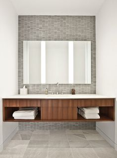 contemporary bathroom by Vinci | Hamp Architects.  Gray/stone tile, white solid surface countertops, wood-toned vanity.