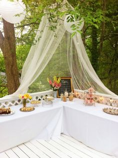 Tables set up on deck with a lace canopy and hanging lanterns. Pretty idea for a vintage tea party/bridal shower.