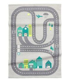 Ljusgrå/Bilbana. En rektangulär matta i bomullskvalitet med tryckt motiv på ovansidan. Mattan har halkskydd under.