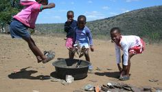Rural children are so enterprising when it comes to developing games. Squashed tins are kicked into an old tyre.