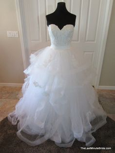 Description Light and dreamy lace and tulle ballgown. This wedding dress features a sweetheart neckline and lace corset bodice on top of a multi layered tulle skirt with scattered lace appliques and h