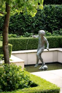 Manicured hedges and white stone make this garden a perfect place for a more traditional water feature, such as this one