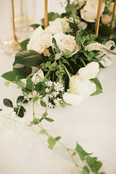 detail of flower cluster at base of tall pedestal arrangement includes white garden roses, white veronica, white ranunculus, button chamomile, orlaya lace, vines, eucalyptus and magnolia.
