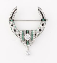 The brooch is great Art Deco onix, emerald and diamond Anneau design from 1919.