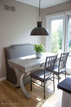 Small eat-in area given a more roomy feel with an upholstered banquette and desk used as a table