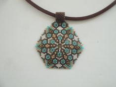 A beautiful peyote pentagon pendant! Made of Miyuki in dark brown, light brown, gold, white, blue ex.... Miyuki chain necklace but it can be removed and