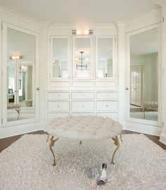 Stunning walk-in closet with floor to ceiling closet cabinets  with mirrored closet doors and crisp white closet crown molding.