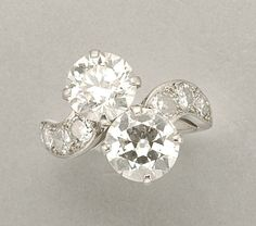 Diamond Crossover Ring   Platinum, set with 2 old European-cut diamonds, approximately 3.75 cts., flanked by 8 round diamonds, approximately .75 ct. signed Cartier, #42-91428, approximately 4.2 dwt