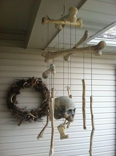 Cute bone mobile idea - Dollar tree always has bags of bones (maybe rub some dark shoe polish on them to make them look old?) #diyhalloweendecorations #halloweenpartysupplies