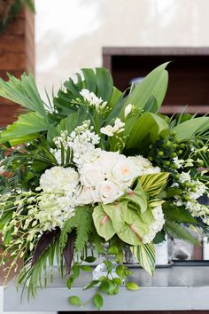 Lush wedding centerpiece idea - white + green  roses, anthurium, orchids, freesias, monstera leaves and other greenery {Elizabeth Garay Photography}