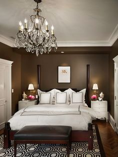 Dramatic bedroom with dark brown walls and white bedding.
