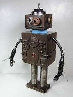 OMEGA Found Object Robot Sculpture Assemblage Found Object Sculpture Assemblage. Approximately 19 tall. Made by Sally Colby. Signed. Made almost entirely of recycled, vintage, and found objects. Parts include a cigar box, hose, wire, vintage radio knobs, a sink strainer, vintage