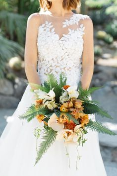 """Megan Gray of Honey and Poppies designed this stunning bouquet. She shared that she wanted something """"lush and abundant,"""" and created this mix to suither vision. Inside were orchids, ranunculus, and celosia, plus pincushion protea and a frame of umbrella ferns."""