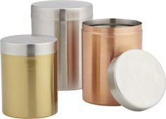 metal ceremony. Trio of copper, gold and brushed silver stainless steel cylinders contain edibles in glistening metallic.  Perfectly sized for coffee, tea or nuts, food-safe and odor-eliminating canisters go for the gleam on the counter, capped off with slick brushed silver. Stainless steel with gold, brass and brushed silver finishHand washWipe cleanwith damp clothMade in India.