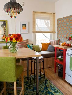 "This looks like a counter height Booth!  ""Go Retro This nifty table offers two seating arrangements. Here, the layout offers stool seating, but it can also be moved in front of the window seat for banquette seating, which provides more seats and additional comfort. Bright, bold colors and a funky chandelier give the tiny kitchen personality."""
