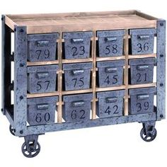 """Showcasing a wood top and 12 numbered drawers, this vintage-inspired kitchen cart offers extra prep space and versatile storage.   Product: Kitchen cartConstruction Material: Wood and metalColor: Natural and grayFeatures:  Charming designEach of the 12 drawers are individually numbered and offer deep storage space Four wheels for easy mobilityDimensions: 32"""" H x 37"""" W x 16"""" D"""