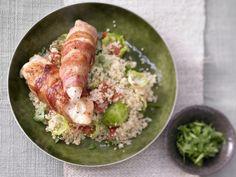 Mit Bacon umwickelt und gebraten gelingt das Hähnchenfilet besonders saftig und zart; angerichtet wird es auf einem Salat aus Couscous und Gemüse.
