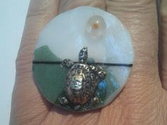 """Anello regolabile con base in vetro opalino ornata con stringers e""""coriandoli"""" di vetro, sormontata da tartaruga finitura argento e cabochon in vetro di Murano trasparente e arancione. Pezzo unico e non ripetibile"""