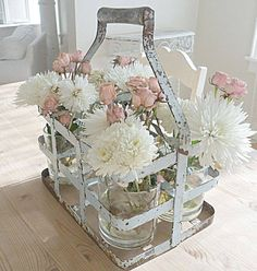 Shabby in love-flowers in glass vases tucked inside a metal basket