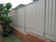 coping with a slope by adjusting both retaining wall and fence