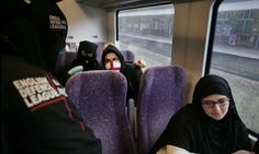 Masked like terrorists, members of Britain's newest and fastest - growing protest group intimidate a Muslim woman on a train en route to a v...