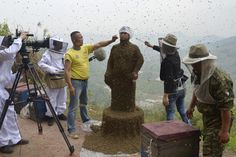 Assistants use burning incense and cigarettes to keep bees away from She Ping's face as his bee suit builds on April 9, 2014.