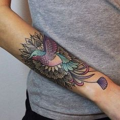 Drawn on the upper part of the forearm, this image is colorful and enticing. It shows a peacock surrounded by colorful and geometric shapes. The peacock's tail extends from the tattoo right into the wrist area. This makes it more attractive as a bird tattoo for women. #tattoofriday #tattoos #tattooart #tattoodesign #tattooidea