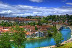 Beautiful skyline over the old town of Bern Switzerland, with its picturesque vistas of terracotta rooftops, & the sparkling blue waters of the Aare river!