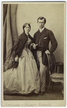 Very handsome man, lady with checked dress and lace shawl pinned at neck. Are those pockets on the skirt front?