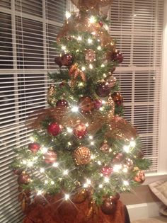 Christmas tree with brown, gold, maroon balls.  Pine cones added for charm
