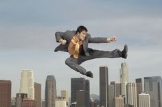 Business man doing martial arts mid-air above city stock photo , Martial Arts, City Photo, Psychology, Wellness, House Design, Stock Photos, Canning, Couple Photos, Business