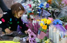A young girl places a rock on a sign at the makeshift memorial outside of the District Office of U.S. Rep. Gabrielle Giffords (D-AZ) a day after a gunman opened fire during a public event entitled 'Congress on your Corner' at the Safeway store on West Ina and North Oracle roads on January 9, 2011 in Tucson, Arizona. Getty Images / Kevin C. Cox