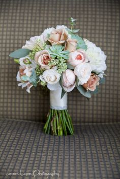 BG400 A loose bouquet of ivory, peach david austin roses`s, latte julia rose`s,coral lisianthus, white dahlia`s and green succulents with a touch of silver native foliage