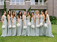 Bridesmaids in seafoam dresses with white orchid bouquets