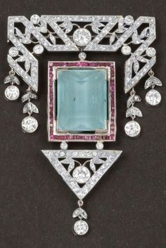 An Art Deco gold, diamond, aquamarine and ruby brooch. Centring a rectangular aquamarine framed by calibré rubies, surmounted by stylised geometric foliate and swag set with brilliant-cut diamonds, suspending a triangular pendant with foliate motif set with brilliant-cut diamonds.