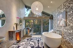 This bathroom has a large accent wall and a whimsical hanging light fixture for a fun and unique design.  See 18 master bathrooms with fireplaces at http://www.homestratosphere.com/master-bathrooms-with-fireplaces/  Source: http://www.zillow.com/digs/Home-Stratosphere-boards/Luxury-Bathrooms/