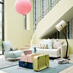 Create a relaxed living space with the paler end of the pastel spectrum. Fresh lemon-coloured walls and sorbet-shade modern furniture make a subtle but stunning statement in this living space. A run of fabric covering one wall of the staircase offers a bold and unusual finish