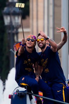 Neymar Santos Jr and Claudio Bravo (R) of FC Barcelona take a selfie as they celebrate on an open top bus during their victory parade after winning the Spanish La Liga on May 15, 2016 in Barcelona.