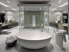 A bathroom features a large round soaking tub and glass-enclosed double shower. Source: http://www.zillow.com/digs/Home-Stratosphere-boards/Luxury-Bathrooms/