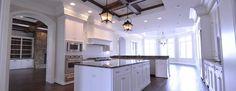 Designer Builders - Aiken SC - white kitchen, island lanterns, stained hitchcock, wood hood, stone fireplace