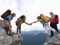 High-Res Stock Photography: Family of hikers helping each other over…