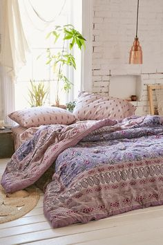 Pink and purple bohemian bedroom with white painted brick wall