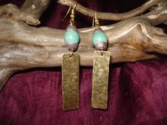 Handmade earrings with hammered bronze sheet and turquoise bead.