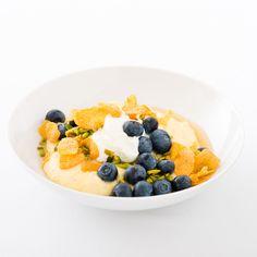 In dieser spätsommerlichen Version des Grießbrei-Klassikers quillt goldgelber Maisgrieß in süßer Milch, serviert mit Blaubeeren, Honig und knusprigen Cornflakes.