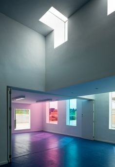 Tinted windows paint the simple, white interior of Educational Centre in El Chaparral with soft hues // Alejandro Muñoz Miranda, photo Fernando Alda Colour Architecture, Spanish Architecture, Education Architecture, Commercial Architecture, School Architecture, Interior Architecture, Interior Design, Colourful Buildings, Co Working